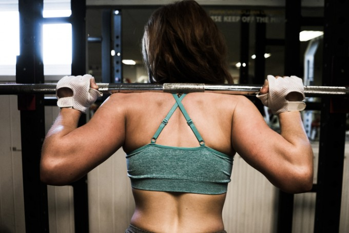 Young woman leaning on a squats rack