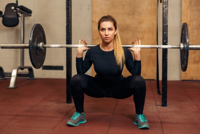 Young strong girl in the gym doing squat in the sport gym. Beautiful athletic woman with beautiful athletic body lifting weights or doing exercises with barbell.