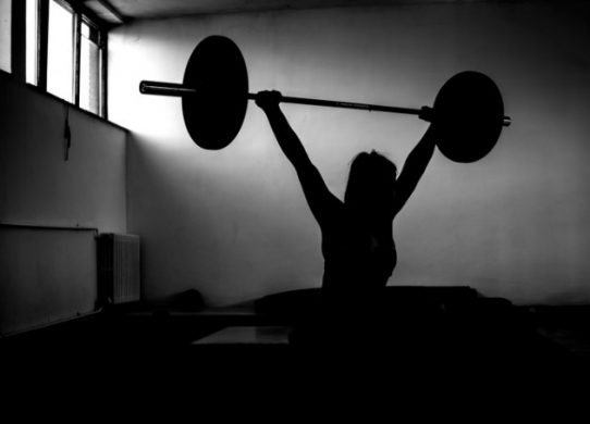 Silhouette of young adult girl doing heavy duty squats in gym with barbell